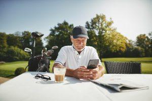 Senior man using smartphone at golf club