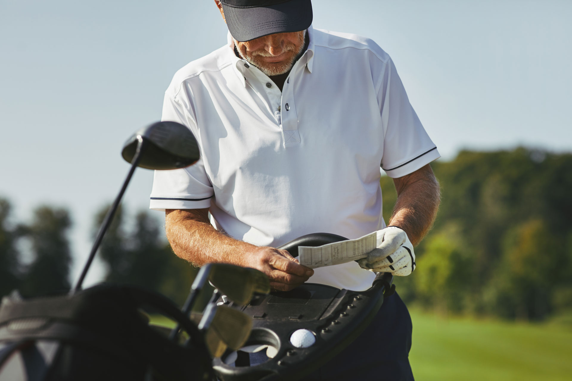 Golfer writing on MiScore card